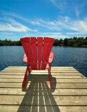 red muskoka chair on lake dock