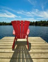red muskoka chair on lake dock